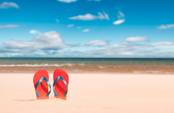 red flip flops on the beach on a sunny day